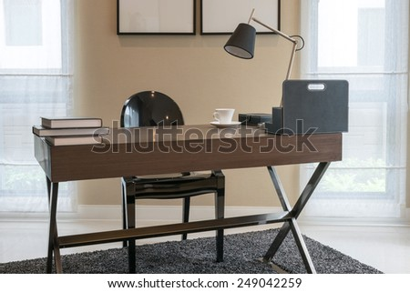 wooden table and books in modern working room interior - stock photo
