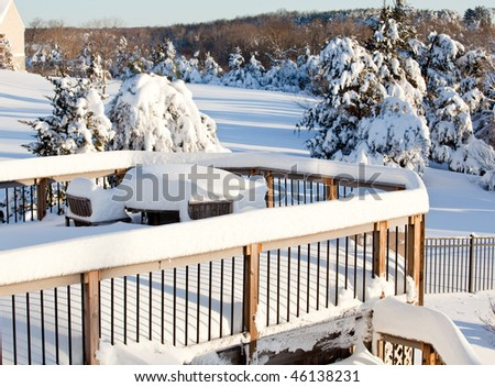 Wooden table and chairs buried deep in snow on deck after blizzard - stock photo