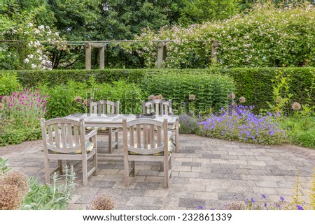 Wooden table and chairs in a beautiful ornamental garden - stock photo