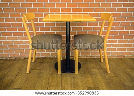 wooden table and chairs in front of historic wall - stock photo