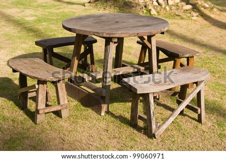 Wooden table and chairs in garden - stock photo