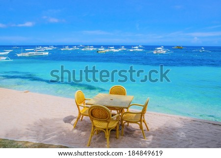 Wooden table and chairs on tropical beach with blue sea - stock photo