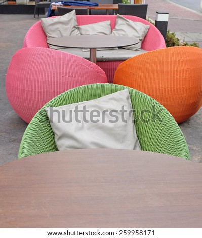 Wooden table and Cushions on a rattan sofa with artificial leather seat  - stock photo