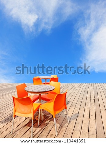 Wooden table and orange chairs on the wooden embankment of a blue sky background - stock photo