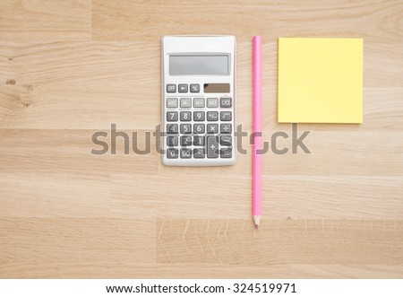 Wooden table at office with calculator, pen and paper. Background with copy space. - stock photo