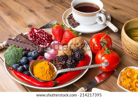 Wooden table filled with antioxidant drinks and food - stock photo