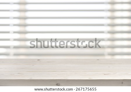 Wooden table from planks on window with venetian blinds background - stock photo