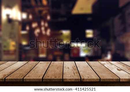wooden table in blur restaurant lights background - stock photo