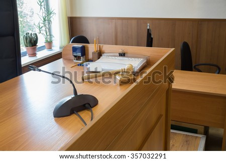 Wooden table in court of law with microphone and gavel - stock photo
