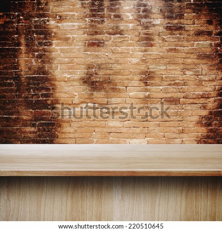 Wooden table in front of brick wall texture background, Grunge industrial interior Uneven diffuse lighting version design component - stock photo