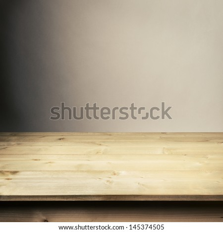 Wooden table in front of wall - stock photo