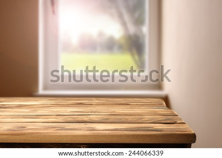 wooden table in interior of room and window of sunny day and tree  - stock photo