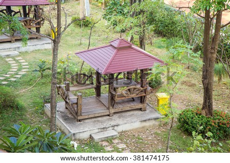Wooden table in the gazebo at a park - stock photo