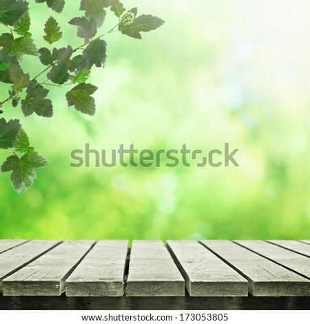 Wooden table near spring meadow with tree leaves on shiny bokeh background - stock photo