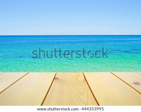 Wooden table on beautiful clear blue ocean background - stock photo
