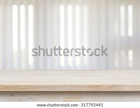 Wooden table on defocuced window with jalousie background - stock photo