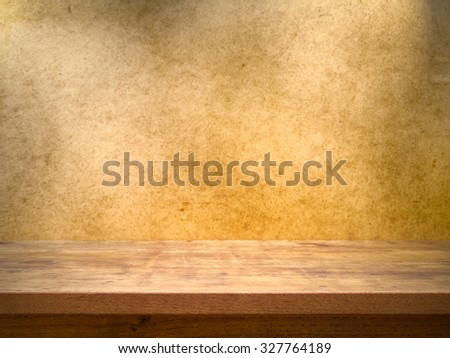 Wooden table on grunge background with dramatic light - stock photo