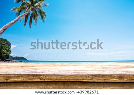 wooden table or wooden mock up over blurred blue sea and white sand beach with clear blue sky background