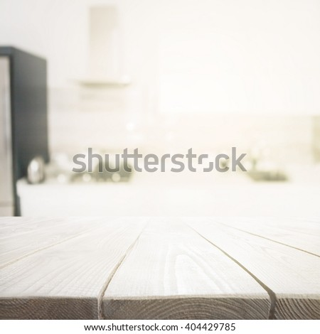 Wooden table over blured kitchen interior background - stock photo