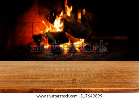 Wooden table over fireplace. Christmas holiday concept - stock photo