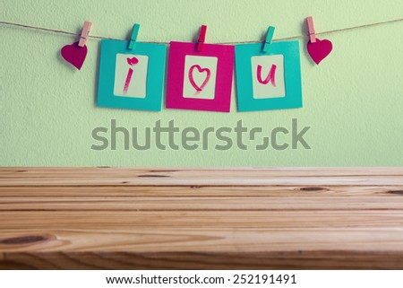 wooden table over vintage i love you write on paper photo frame and red heart over wall background, Valentine concept - stock photo