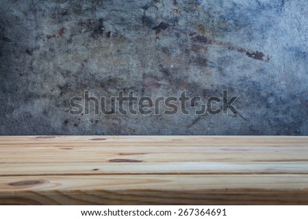 wooden table over wall grunge background with space for text or photo