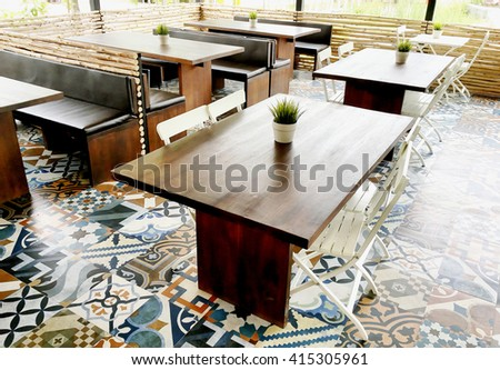 Wooden table set on artistic mosaic tiles - stock photo