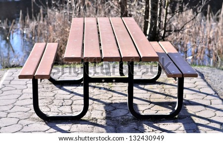 Wooden table side view in the park - stock photo