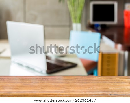 Wooden table top over blurred image of  modern workplace background - stock photo