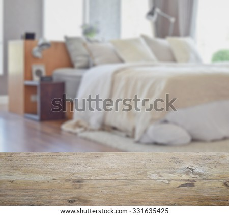 wooden table top with blur of modern bedroom interior design with white pillows on bed - stock photo