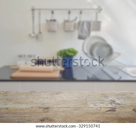 wooden table top with blur of modern ceramic kitchenware and utensils on the counter top - stock photo