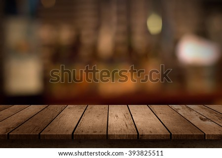 wooden table with a view of blurred beverages bar backdrop - stock photo