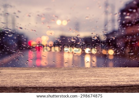 wooden table with blur traffic view through a car windscreen covered in rain for background - stock photo