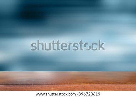 Wooden table with Blurred blue background. - stock photo