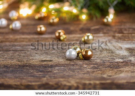 wooden table with defocused christmas  glowing lights and glass balls - stock photo
