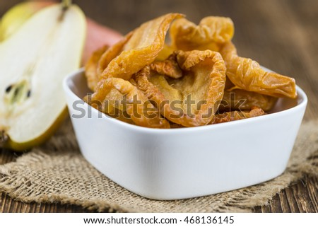 Wooden table with dried Pears (selective focus; close-up shot)