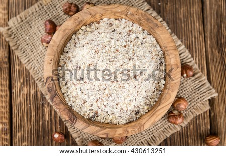 Wooden table with grounded Hazelnuts (close-up shot; selective focus) - stock photo