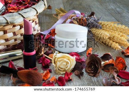 wooden table with items for makeup and fragrant flowers dried