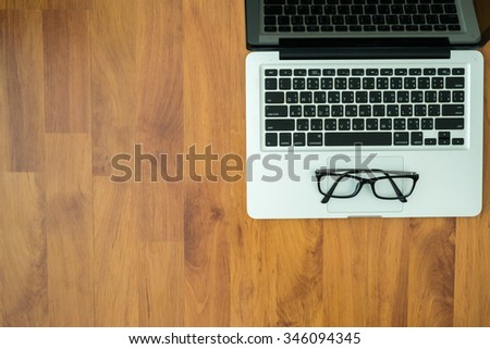 Wooden table with laptop and eye glasses on top. Top view with copy space. - stock photo