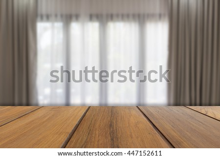 Wooden table with modern gray and white curtains in living room interior - stock photo