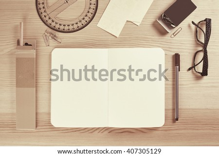 Wooden table with notepad sketchbook pens and office stuff in vintage style - stock photo