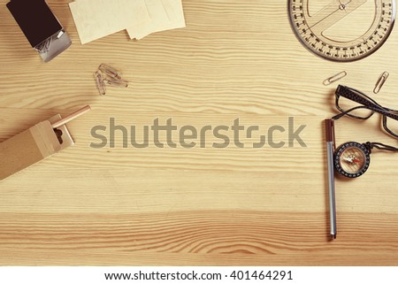 Wooden table with office stuff and compass in vintage style