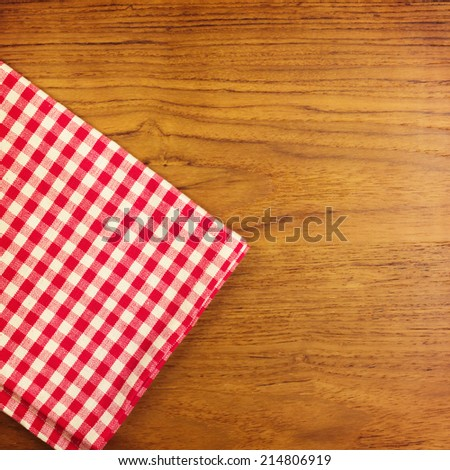 Wooden table with red checked tablecloth