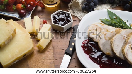Wooden table with roast pork, cheese, wine jelly, grape, strawberry, cherries, currants and spices - stock photo