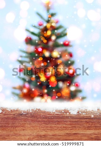 Wooden table with snow place and Christmas tree background with blurred, sparking, glowing. Happy New Year and Xmas theme