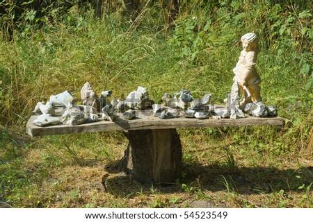 Wooden table with stones in a natural garden - stock photo