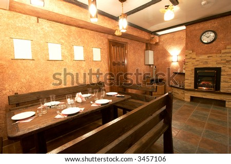 Wooden table with utensils in a room with a fireplace