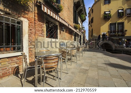 Wooden tables on narrow street among typical colorful houses and small bridge in Venice, Italy. - stock photo