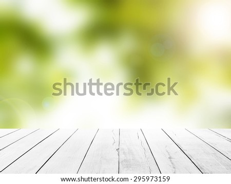 Wooden tabletop foreground with blur green leaf background. Blurry Leaves advertising Flare Sunbeam Rays Abstract Floor Scene Medical Bokeh Sunlight Spring Wood Planks White Greenery Perspective Stage - stock photo
