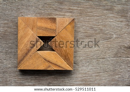 Wooden tangram as square with hourglass inside shape on old wood background